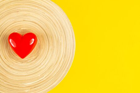 Red heart in wooden dish with yellow background. Stock Photo