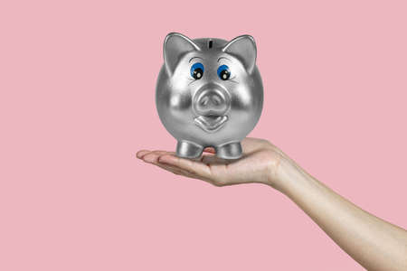 Piggy bank for money safe on woman hand with isolated pink background.