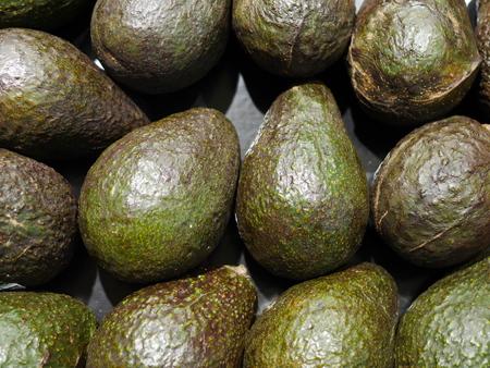 Green Avacados stacked at farmers market Stock Photo