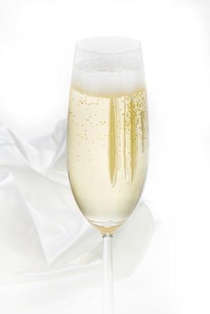 glass of champagne on white velvet photo