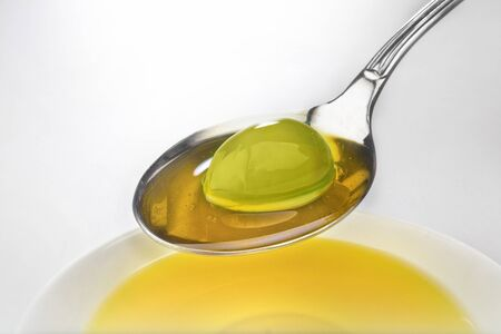studio photography of olive on spoon covered with olive oil Green Olive photo