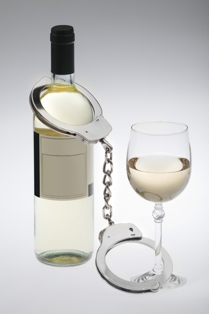 studio closeup photo of wine glass connected with hanging cuffs to bottle of wine on grey background addiction to alcohol photo