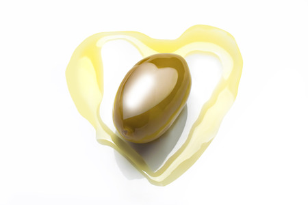 studio photo of olive in heart shaped olive oil with heart shaped reflection of soft box Banco de Imagens
