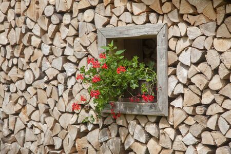 a window stocked with firewood decorated with red flowers