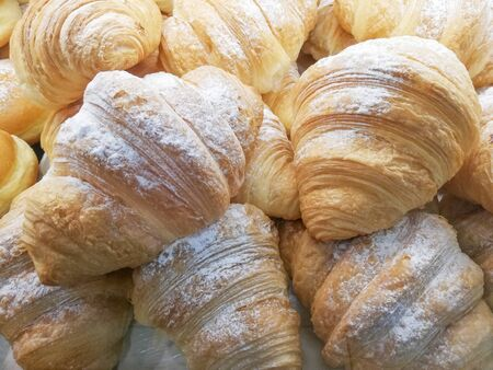 fresh croissants stuffed with cream or jam in a bakery on a shelf ready for sale