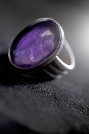 silver ring with a purple stone on dark background