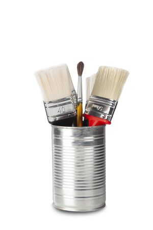 studio shot of brushes of different colors in tin can elaborated on white background with shadow under