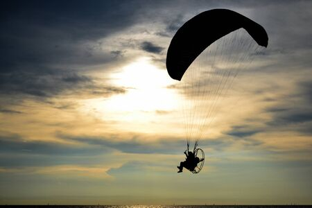 Silhouette one paramotor over sea and sunset sky Stock Photo