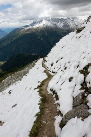Snowy footpath on the slope in summer Alps