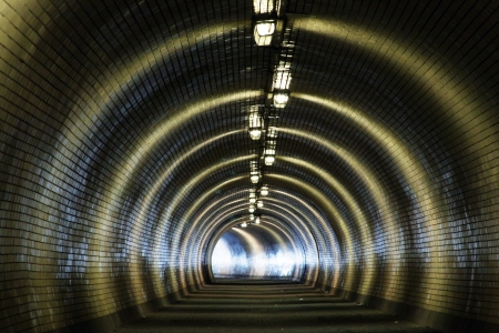 Perspective View Through a Dark Tunnel With the Light at The End Stock Photo