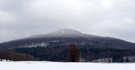 Symmetrical Mountain in Winter Landscape With White Cap  Studenec Czech Republic  photo