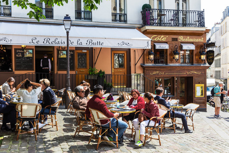 restaurant tables: Paris, France - June 28, 2016: A traditional restaurant in Paris, in the Butte Montmartre. Parisians and tourists enjoy food and drinks under the sun. Montmartre area is most popular destinations in Paris, has lots of cozy cafes, restaurants, bistros, nig