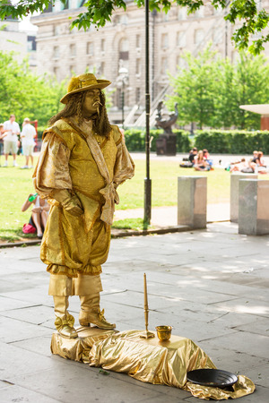 passerby: London, UK - June 11, 2006: City street performance of gold painted actor in suit of a king of 17 century. Living statues is the entertainment for passerby.