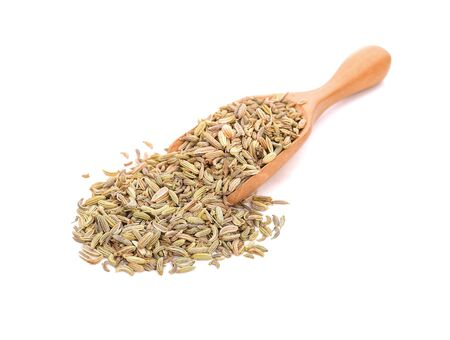 Dried fennel seeds in a wooden spoon isolated on white background