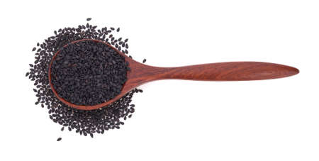 Black sesame in wooden spoon isolated on white background.
