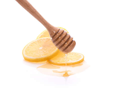 Honey dripping on fresh lemon isolated white background