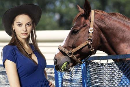 Cowgirl feeding grass her horse  photo