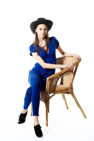 Girl in cowboy hat on straw chair photo
