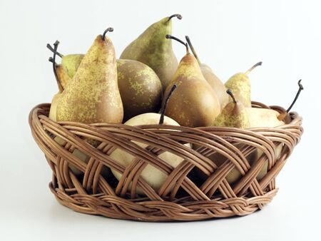 pear: Peras en cesta de paja en fondo blanco Foto de archivo