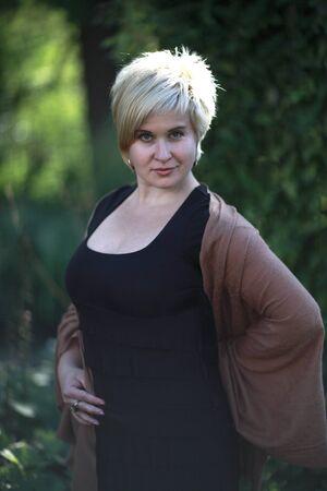 looking ahead: Blonde posing and looking ahead in garden