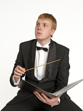 memorise: Young music conductor with score and baton