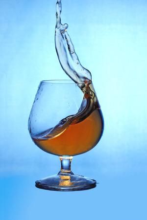 cognac: Cognac splash in goblet on blue