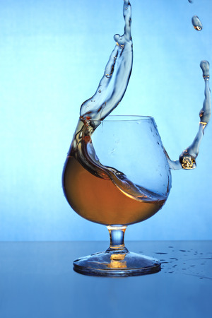 cognac: Cognac pouring out of glass - wave and drops