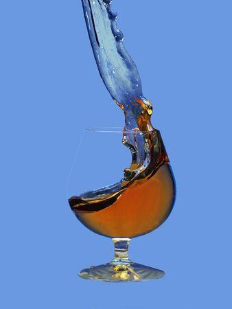 Nice splash brandy in glass on blue background