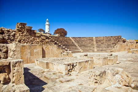 The ancient amphitheatre in Paphos with lighthouse on the background