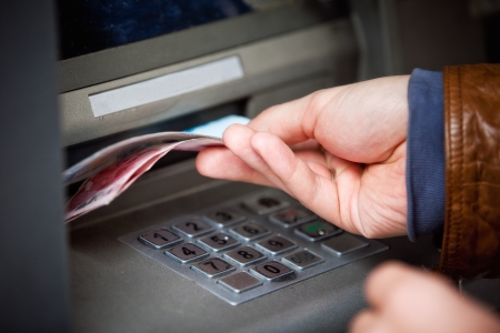 bankomat: Hand taking out cash from machine Stock Photo