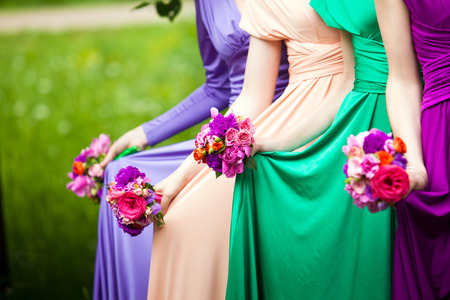 Bridesmaids in colorful dresses with bouquets of flowers Stock fotó