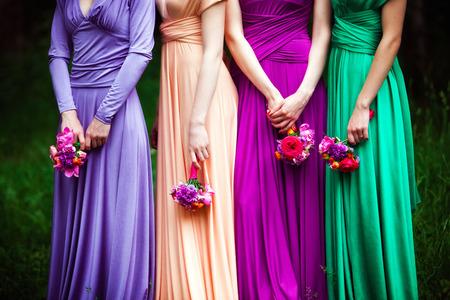 feier: Brautjungfern in bunten Kleidern mit Blumensträußen Lizenzfreie Bilder