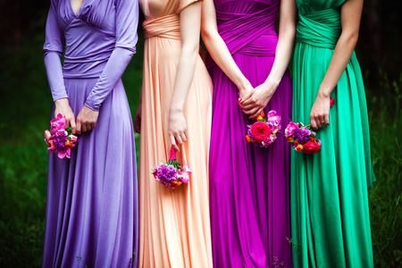 to dress: Bridesmaids in colorful dresses with bouquets of flowers Stock Photo
