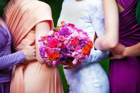 bridesmaids: Bridesmaids in colorful dresses with bouquets of flowers Stock Photo