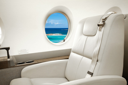 Aiircraft porthole with view of sea and beach resort, flight by business class Stock fotó