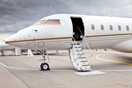 bombardier: White private business jet and open ladder at the airport Stock Photo