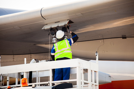 Aiport worker refuelling the aircraft