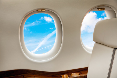 private jet: Aircraft porthole with blue sky view close up