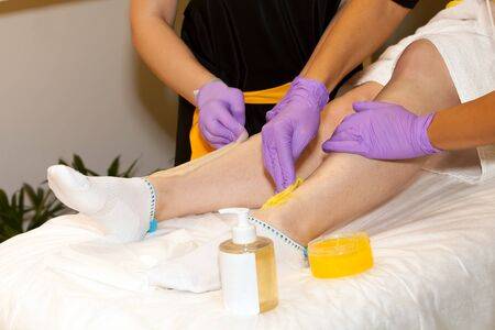 sugaring: Legs sugaring procedure in spa salon close up view