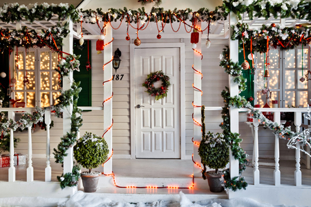 Entrance to the house with porch decorated for christmas and New Year holiday