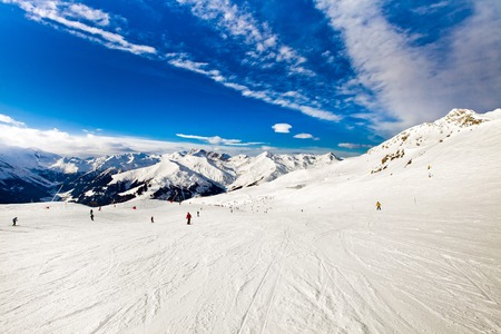 Ski resort in the Alps. Panoramic view of the mountains. People skiing and snowboarding. Mayerhofen, Austria Stock Photo