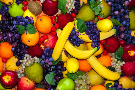 apples and oranges: Colofrul background of different fruits - bananas, grapes, apples, oranges