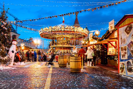 Moscow, Russia - December, 2015: People on Christmas market on Red Square in Moscow city center, Decorated and illuminated Red Square for Christmas in Moscow. Carousel swings on Christmas bazaar Editorial
