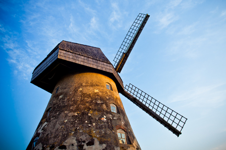 Traditional Old dutch windmill Cesis, Latvia against blue sky with white clouds Stock Photo