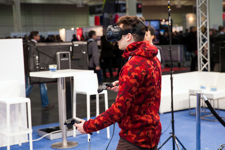 developed: Hannover, Germany - March, 2017: Man playing video game in virtual reality headset and handheld controllers developed by HTC Vive on exhibition Cebit 2017 in Hannover Messe, Germany Editorial