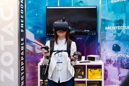 htc: Hannover, Germany - March, 2017: Girl playing video game in virtual reality headset and handheld controllers developed by HTC Vive on exhibition Cebit 2017 in Hannover Messe, Germany