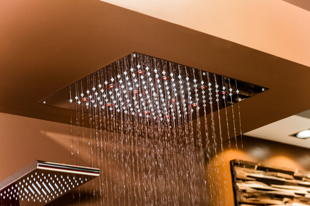 jet stream: Chrome shower sprinkler head with falling water drops Foto de archivo