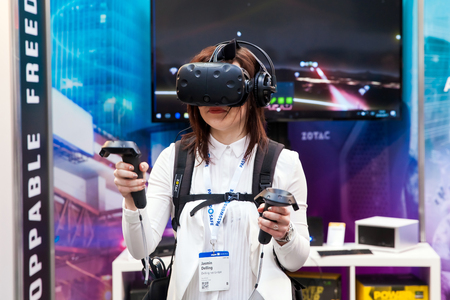 developed: Girl playing video game in virtual reality headset and handheld controllers developed by HTC Vive on exhibition Cebit 2017 in Hannover Messe, Germany