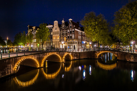street shot: Night shot of the city, many bicycles on the bridge on Amsterdam canal, Netherlands