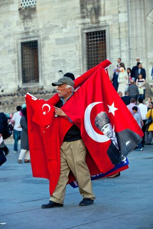 Istanbul, Turkey - April, 2013: Man with turkish flags on the square in Istanbul, Turkey